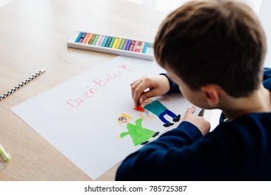 Happy Polish child drawing a greeting card for his grandma. Polish word Grandmother Day!