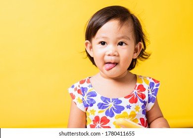 Happy portrait Asian baby or kid cute little girl attractive laugh smile wearing dick pattern shirt holds and eating sweet wooden ice cream, studio shot isolated on yellow background, summer concept