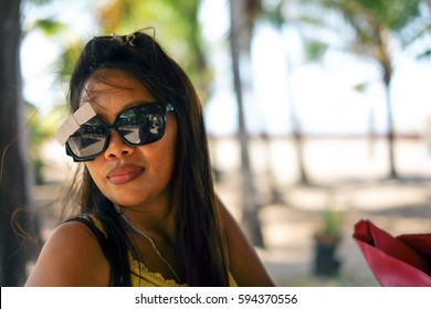 Happy portrait of Asian woman with sunglasses in summertime on the beach