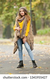Happy Portrait fashion of a beautiful young Caucasian woman with a red cap and scarf and yellow pullover in autumn park,red green yellow threes. Autumn, season and people concept.Autumn lifestyle