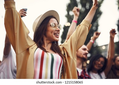I am happy. Portrait of young stylish lady in hat raising hands and looking away with smile. Her friends standing on blurred background