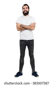 Happy positive bearded hipster in white t-shirt and tight jeans with crossed arms. Full body length portrait isolated over white studio background.