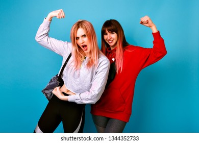 Happy positive best friends sister women posing at blue studio background, hipster sportive casual style , going crazy and imitating biceps, funny grimaces, fitness time .