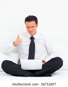 Happy positive business man with thumb up sitting on couch in hotel