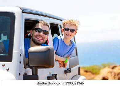 happy positive caucasian boy in sunglasses and his father peeking out of the car window, tropical family vacation or active road trip concept, copy space on right