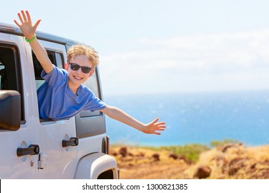 happy positive caucasian boy in sunglasses peeking out of the car window with his hands up in the air, tropical family vacation or active road trip concept, copy space on right