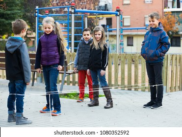 Happy positive children playing rubber band jumping game and laughing outdoors