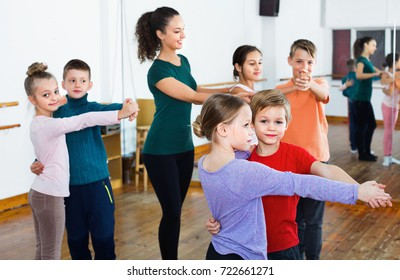 Happy positive children studying of partner dance  at dance school