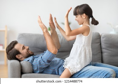 Happy positive diverse family at home, young smiling father lying on couch having fun with daughter playing pat-a-cake game clapping hands giving high five. Family weekend leisure activities concept