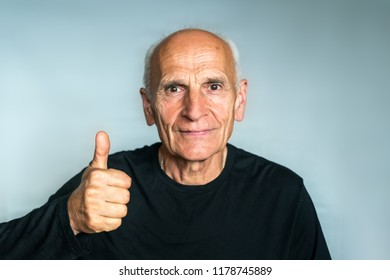 Happy positive elderly man in a black shirt, thumb up, everything's cool.