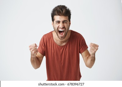 Happy positive excited young man clenching fists and screaming, wearing casual t-shirt glad to hear good news, celebrating his victory or success. Life achievement, goals and happiness concept.