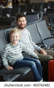 happy positive family of two, father with a beard and little son, at the airport waiting for departure, travel and vacation concept