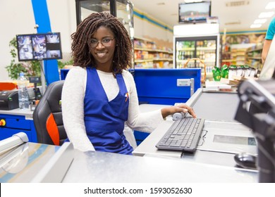 Happy positive female cashier working in grocery store. Young African American woman wearing uniform, posing at cash register counter in supermarket. Cashier concept