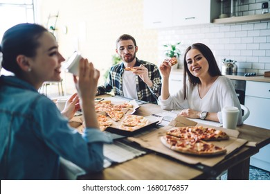 Happy positive friends in casual wear eating tasty pizza and relishing beverage while chilling at table in light modern kitchen
