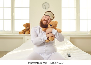 Happy positive funny fat grown up adult man with ginger beard in white pajamas and sleep mask sitting on bed in bedroom, cuddling favorite teddy bear like a baby and smiling. Immature behavior concept