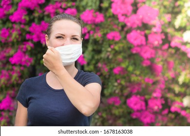 Happy positive girl, young beautiful woman takes off protective sterile medical mask from face outdoors, smiling. Happy end. Pollen allergy. Victory over coronavirus. Pandemic Covid-19. Flowers