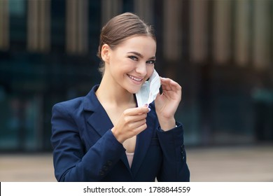Happy positive girl, young beautiful pretty business woman takes off protective sterile medical mask from face, smiling. Victory over coronavirus. Pandemic Covid-19.