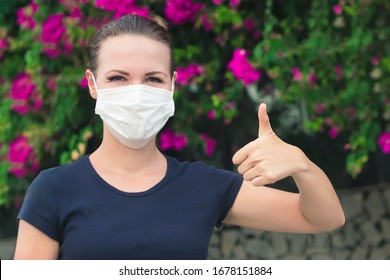 Fröhliches positives Mädchen, jung fröhliche schöne Frau in einer sterilen Schutzmaske auf ihrem Gesicht Blick Kamera draußen, Lächeln, zeigen Daumen nach oben, wie Geste. Alles Gute zum Schluss. Pollenallergie