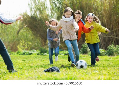 Happy positive  kids playing football outdoors in sunny day