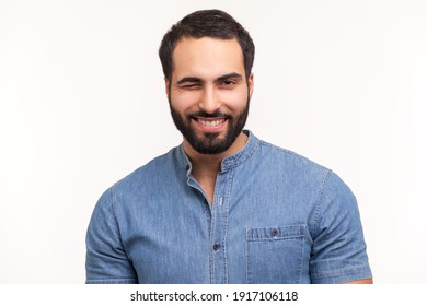 Happy positive man with beard winking looking at camera with playful smile, flirting, has good mood, waiting for date. Indoor studio shot isolated on white background