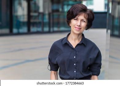 Glückliche erwachsene Geschäftsfrau im Freien Geschäftszentrum lächelt, Blick auf die Kamera. Portrait der Brunette Frau mittleren Alters, schöne Dame mit Kopienraum. Attraktive weibliche Haltung