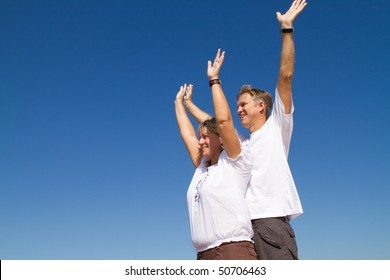 happy positive mature couple arms open, background is blue sky