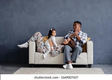 Fröhliche positive gemischte Rasse Familie afrikanische amerikanische junge Vater asian Mutter und kleine Tochter ruhen zu Hause auf dem Sofa auf dem Hintergrund einer grauen Wand. Werbefläche