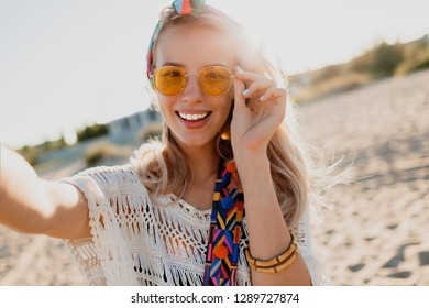 Happy positive mood. Blond playful girl with stylish headband making self portrait on tropical sunny beach. Travel and freedom concept. Bohemian outfit.