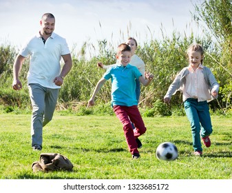 Happy positive mother and father with two cheerful kids playfully running after ball outdoors