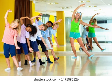 Happy positive preteen dancers practicing dance routine with female choreographer in modern studio