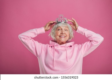 Happy positive senior model put tiara on head and smile. Look straight on camera and smile. Wear pink hoody. Feel like a princess. Isolated over pink baclground