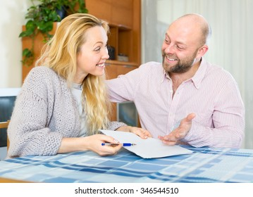 Happy positive smiling couple looking at each other and holding papers in their hands