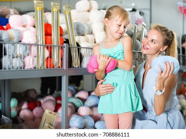 Happy positive smiling female with girl in the shop choosing thread for knitting