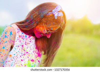 Happy positive smiling fun woman wearing sunglasses all stained with colorful paint celebrating laughs on Holi festival party. On color dust smoke powder cloud background in sunny park field outdoor