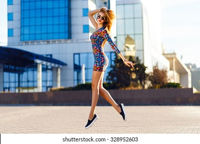 Happy positive summer portrait of cute sexy woman in bright mini dress jumping on the street, sunny day, urban style, make up, fashion accessorizes .