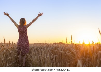 Happy positive woman full of vitality raising hands and facing the sun in a wheat field at sunrise