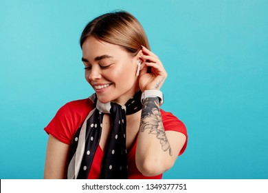 Happy positive young woman look down and smile. She pose on camer and touch hair with hand. Isolated over blue background