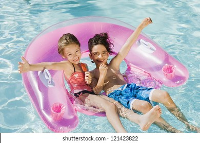 Happy preadolescent friends enjoying in swimming pool