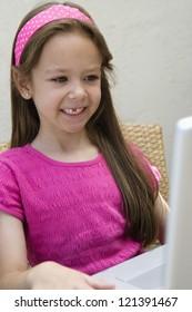 A happy preadolescent girl using laptop