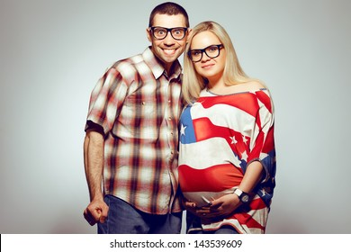Happy pregnancy concept: portrait of two funny hipsters (husband and wife) in trendy glasses and clothes. Wife holding her belly and husband getting crazy of being father. Studio shot