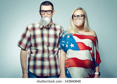 Happy pregnancy concept: portrait of two funny hipsters (husband and wife) in trendy glasses and clothes playing with their bubble gums. Copy-space. Studio shot