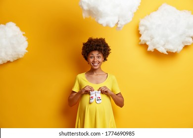 Happy pregnancy and expectation concept. Smiling future expectant mother holds baby booties socks over abdomen, anticipates child, being pregnant, dressed in yellow dress, fluffy white clouds above