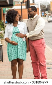 Happy pregnant African American couple walking and talking.