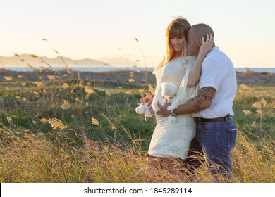 Happy pregnant couple outdoors field