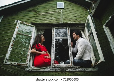 Happy pregnant couple sits on a windowsill in an old wooden house