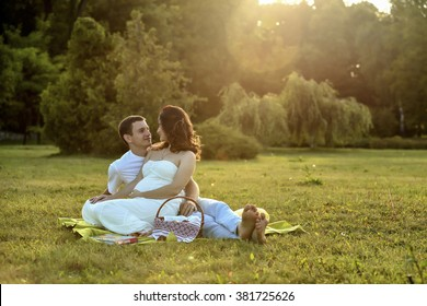 Happy pregnant couple sitting on the banch in park