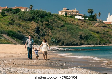 Happy pregnant couple with their son enjoying sunny day and walk on the coast in Spain.
