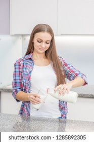 Happy pregnant girl pours milk into a glass