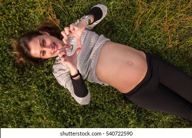 happy pregnant girl relaxing on the grass.