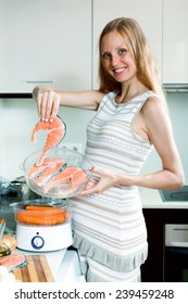 happy pregnant housewife cooking fresh vegetables with electric steamer at kitchen
